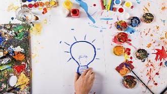 Picture of a hand drawing a lightbulb with paints and other art supplies around the image