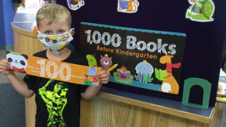 "Boy holding up banner that says 100 standing next to ""1000 Books Before Kindergarten"" poster"