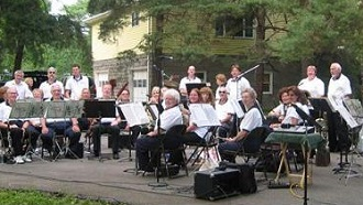 Picture of the members of Cortland Community Band smiling with their instruments