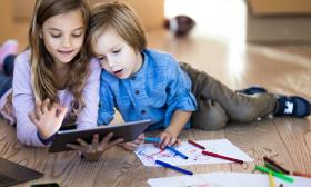 two kids looking at an ipad