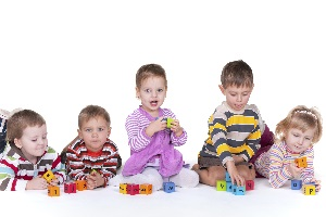 5 kids sitting in a row playing with blocks