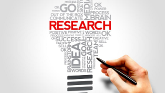 """Word cloud shaped like a light bulb with the word """"research"""" large and in red"""