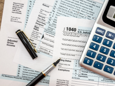 IRS tax forms laid out on a table with a pen and calculator on top of them